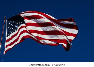 windy day clear blue skies with American flag blowing on a flag pole. Room for text