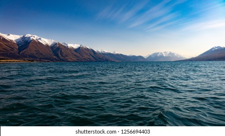 a windy day makes the lake water choppy backed by snow capped mountains and a windy blue sky