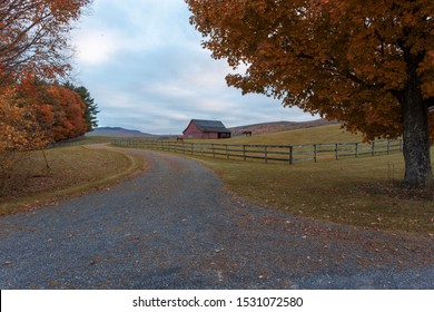 A windy dirt road leading to a Vermont horse farm during fall foliage in October