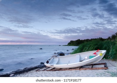 windy evening in the sea coast when the sun sets in. white fishing boat waiting for the sea. long exposure.