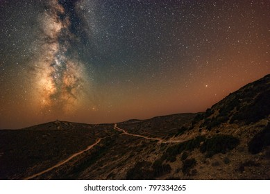 Windy milky way in red airglow above sea island