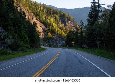 Windy scenic road around the mountains during a vibrant summer sunrise. Taken in Glacier National Park of Canada near Revelstoke, BC.