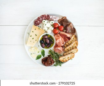 Wine appetizer set. Cherry-tomatoes, parmesan cheese, meat variety, bread slices, dried tomatoes, olives and basil on round ceramic plate over white wood backdrop, top view