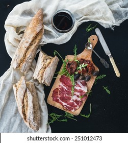 Wine appetizer set: a glass of red wine, vintage dinnerware, white towel, baguette pieces, dried tomatoes, olives, smoked meat and arugula on a rustic wooden board over a dark background. Top view