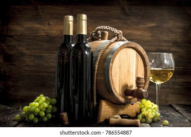 Wine background. A barrel of white wine with branches of green grapes. On a wooden background.