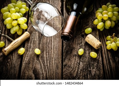 wine background of open wine bottle, wine glass and branches of white grapes on a dark wooden rustic background with blank space for a text