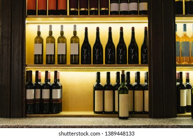 Wine bar illuminated shelf with bottles of wine in a row