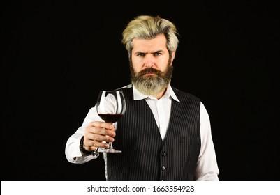 Wine bar or winery. drink degustation. Bearded businessman in elegant suit with glass of wine. Sommelier tastes expensive drink. Elegant waiter drink red wine. working in wine cellar.