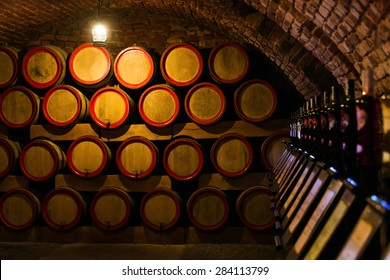 stacked oak barrels. Wine Barrels In The Antique Cellar. Cavernous Cellar With Stacked Oak For Maturing