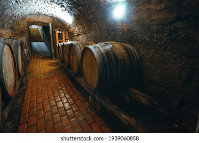 Wine barrels in a wine cellar. Small production. Underground tunnel. Storage of finished products. deep sharpness on a wide angle lens
