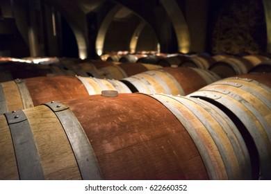 Wine barrels with red stripes in a dark wine cellar.