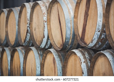 Wine barrels stacked in the wine cellar on a factory.