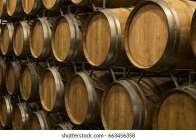 Wine barrels stacked in a old cellar at winery. Wooden barrels of wine in vineyard. A lot of wine barrels stacked in a cellar.