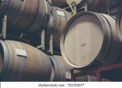 wine barrels stacked on racks in a California warehouse. The process of aging wine.