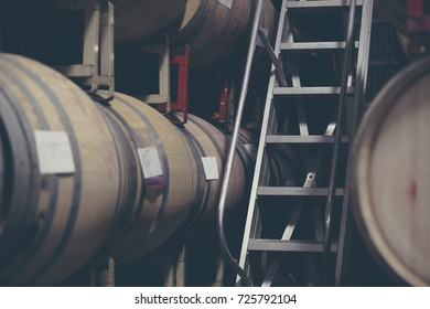wine barrels stacked on racks in a California warehouse with a ladder. The process of aging wine.