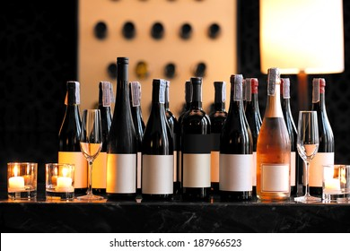 Wine bottle with candle and empty wine glasses on counter bar