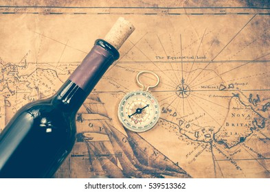 wine bottle and compass on vintage map