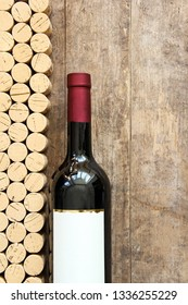Wine bottle with corks against rustic wooden board for text copy space