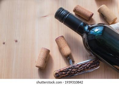 Wine bottle, corks and corkscrew, wooden background