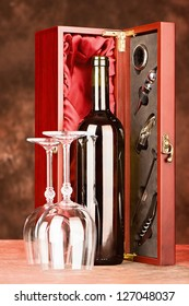 Wine bottle and cups in front of wooden wine case