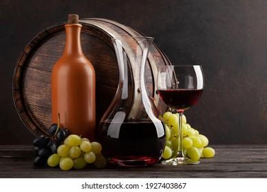 Weinflasche, Dekanter, Glas Rotwein, Weintrauben und altes Holzfass. Mit Kopienraum