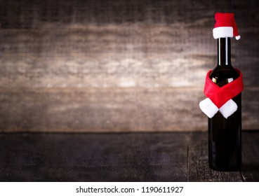 Wine bottle decarated with santa claus hat and scarf on wooden background, nobody