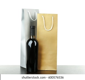 Wine bottle and gift bags on white background
