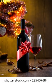 Wine bottle gift and wine glass filled with red wine, christmas tree and dry leaves on background.