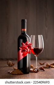 Wine bottle gift with red wine glass, autumn leaves and wooden surface on background.
