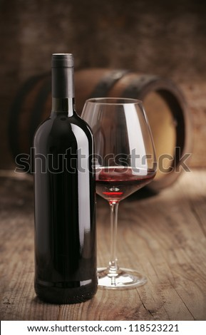 Wine bottle with glass,  barrel on background