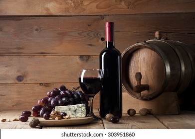 Wine bottle with glass, bunch of grapes, blue cheese, walnuts and wooden barrel on old wooden background
