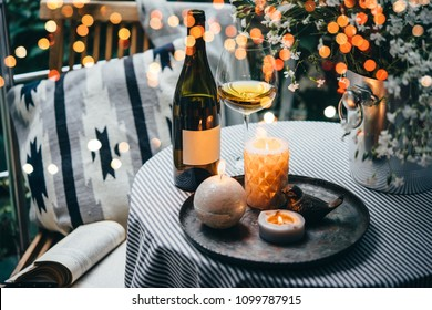 Wine bottle, glass and candles on a beautiful terrace or balcony