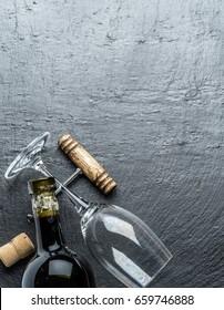 Wine bottle, wine glass and corkscrew on the graphite board.