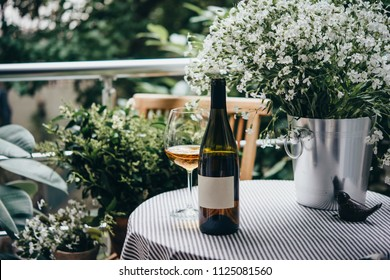Wine bottle, glass and flowers on a beautiful terrace or balcony