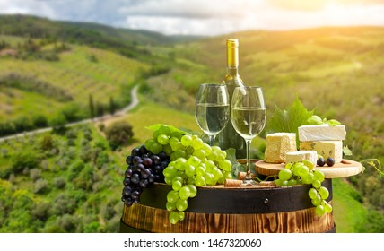 wine bottle and wine glass on wodden barrel. Beautiful Tuscany background