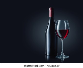 Wine bottle and glass with red wine on dark glossy background.