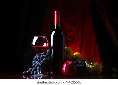 Wine. Bottle and glass of red wine with ripe grapes still life. Red wine on a dark background.