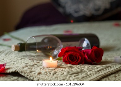 Wine bottle glass and roses on bed with tea lights