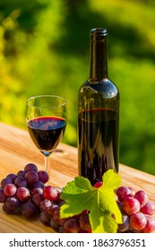 wine bottle and grapes on wooden table, outdoor