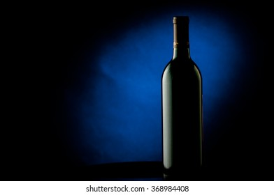 Wine bottle isolated on a black background with a splash of blue