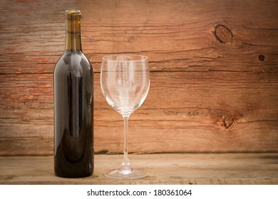Wine bottle with the label removed standing alongside an elegant wineglass against rustic wooden boards with copy space