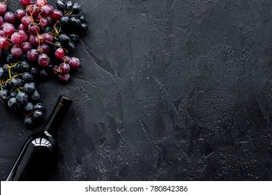 Wine bottle near bunches of red and black grapes on black background top view copyspace