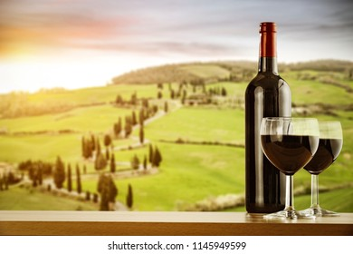 Wine bottle on desk with free space for your decoration and Tuscany landscape.