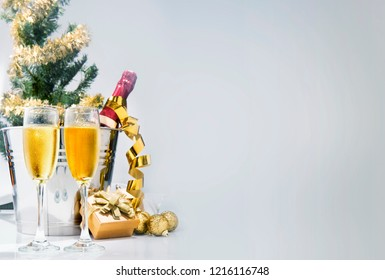 Wine bottle on ice bucket and a pair of glasses with christmas decoration. Party and celebration concept