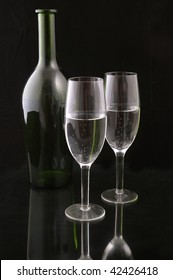 Wine bottle and pair of champagne flutes against a black background