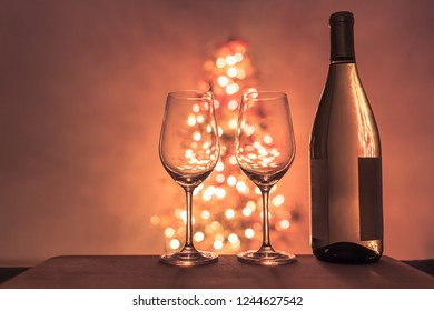 Wine bottle and pair of glasses next to Christmas tree. Romantic holiday background.