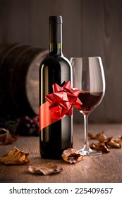 Wine bottle with ribbon gift, wineglass with red wine and barrel on background.