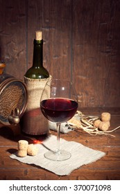 Wine bottle and small barrel with glass on old wooden background. Vintage colors.