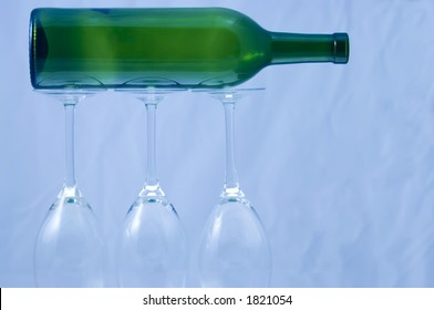 Wine bottle supported by three wine glasses