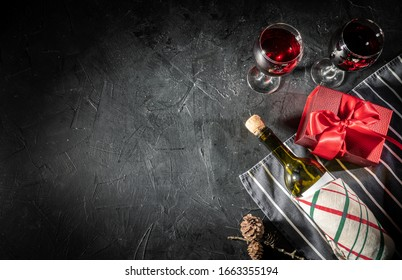 Wine bottle and valentines day gift box on dark background with copy space